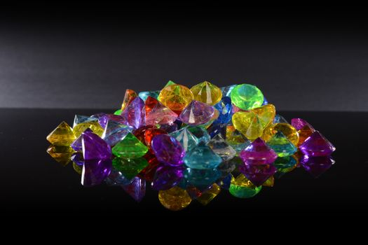 A pile of gemstone variations over a black reflective surface.