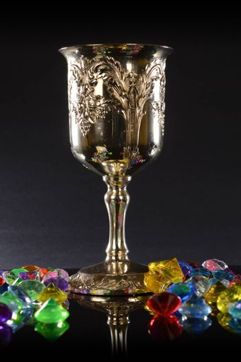 A silver wineglass with several pieces of gemstones over a black background.