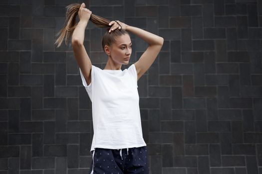 Woman Ties her hair in a ponytail before morning workout black wall background