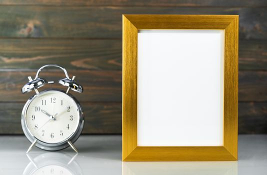 Picture mock up with golden frame and alarm clock over table with wood wall background