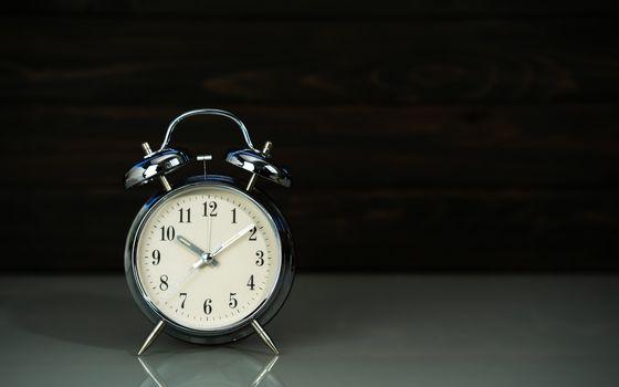 Retro alarm clock on table near wood background