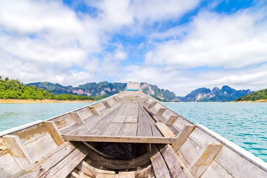 Wooden Thai traditional long-tail boat on a lake with mountains