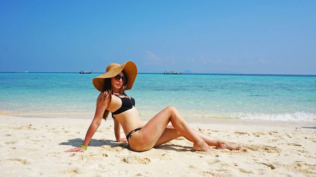 The girl in the hat and swimsuit on the beach. Glasses on. European woman on the beach with white sand. The water is turquoise with a blue tint. Photo shoot model. White sand and blue sky. Paradise.