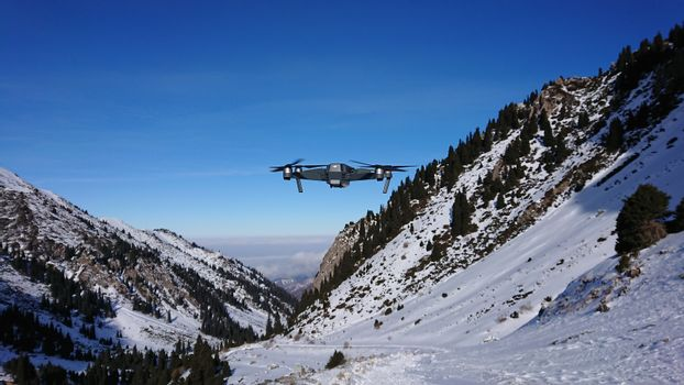 DJI Mavic Pro in the air in the winter gorge. A professional quadcopter takes pictures of nature. Mountainous terrain, winter, lots of snow. Pine trees grow on the rocks. The Mountains Of Almaty.