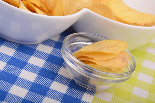 Crispy potato chips in a glass bowl on old tablecloth