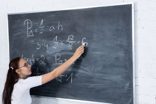Mathematical task. Blackboard. Young teenage girl. He solves the task standing at the school board. I write with chalk on the blackboard.
