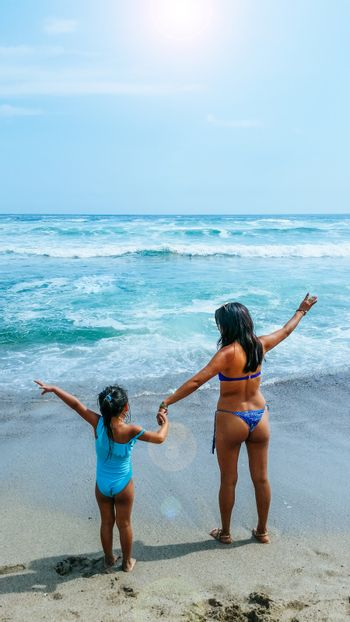 Mom and daughter are resting on the beach.