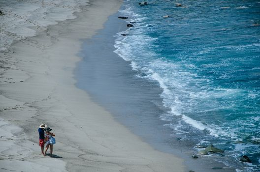 A couple, man and woman, on the shore of a beach taking pictures