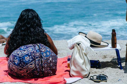 Woman resting enjoying summer on the beach, sitting on her back
