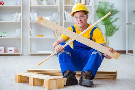 Young man assembling wood pallet