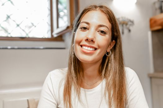 Confident young beautiful woman smiling looking at the camera for a video call conference in her home - Portrait of a cute long hair female alone person at home - New normal social communication