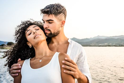 Heterosexual mixed race couple in romance scene at sunset with vintage photo effect filter - Handsome Caucasian guy embracing from back his Hispanic girlfriend with closed eyes - Focus on curly hair