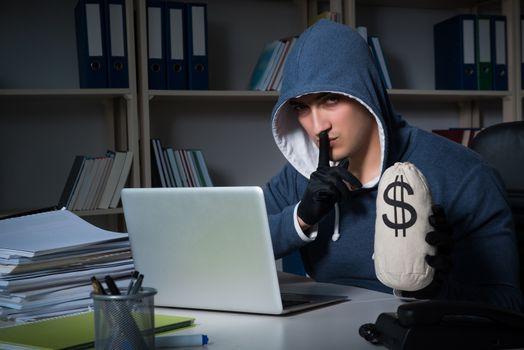 Young hacker hacking into computer at night