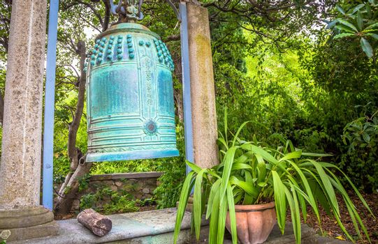VENTIMIGLIA, ITALY - CIRCA AUGUST 2020: old Japanese bell located in Hambury Gardens and finely crafted in bronze. It seems to come from a Buddhist shrine destroyed by a fire in central Japan.