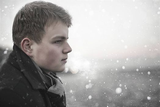 Portrait of handsome young Caucasian man looking away in a winter background. Concept about lifestyle, people, nature and travel.