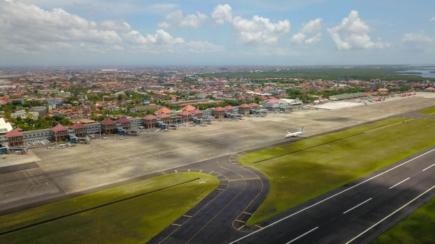Airport - aerial view with runways, taxis, grass and air-crafts. Aerial view to Ngurah Rai airport. The plane goes down the runway