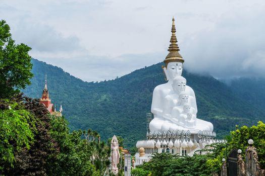 White Buddha Statue and cloud background at Wat Prathat Phasornkaew Thailand
