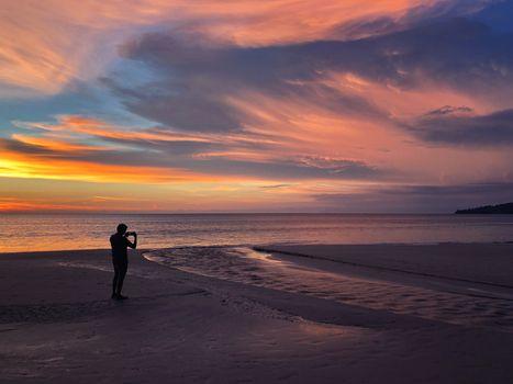 Panoramic view of sunset a man taking photo at Karon beach in Phuket, Thailand
