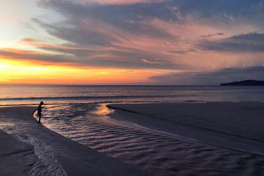 Panoramic view of sunset kid playing on the beach at Karon beach in Phuket, Thailand