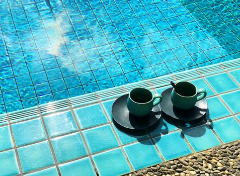 Two vintage cup of hot coffee  beside the pool.
