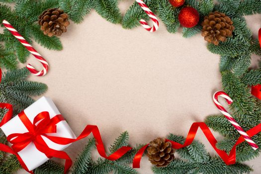 Christmas noble fir tree twigs gift and decorations on brown paper background with copy space for text