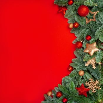 Christmas fir tree branches and baubles decor border frame on red background with copy space for text