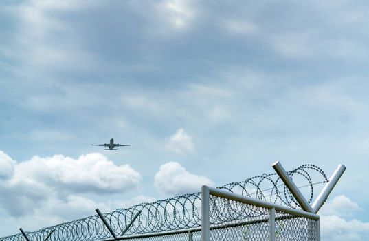 Airplane flying on blue sky and white clouds above metal fence. Aviation business. Commercial plane. Air transportation. Fence for safety and security. Aviation business. Travel by plane.