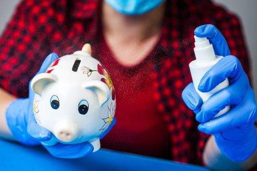 Coronavirus COVID-19 corona virus disease global pandemic outbreak,person holding piggy bank wearing blue surgical protective gloves,disinfecting it with antibacterial sanitizer spray,economy crisis