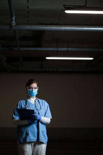 Portrait of frontline EMS key worker in dark hallway,in PPE blue uniform,protective face mask,goggles & gloves,holding clipboard patient form,worried stressed & overworked UK NHS ICU medical staff