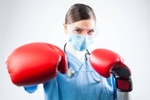 Young female caucasian doctor wearing blue uniform and red boxing gloves, professional and confident, fighting off a disease, immunity and immune system antibodies overcoming viral antigens concept