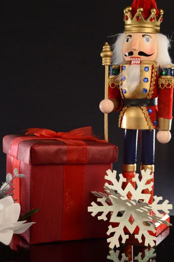 A Christmas holiday Nutcracker stands next to a red gift for the season of giving.