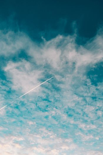 Plane flying on the sky between the clouds in a minimalistic image with a saturated blue color