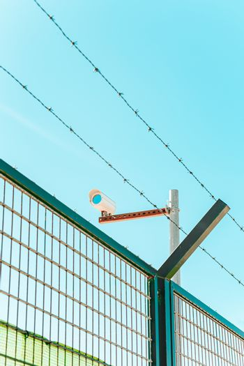 Minimalistic and colorful shot of a surveillance camera with a wall and a barbed wire