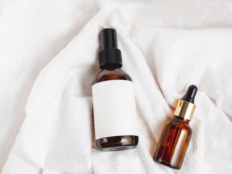 Top view on two glass bottles on white fluffy towel. Essential oil and cosmetic serum with clear labels on crumpled bathrobe