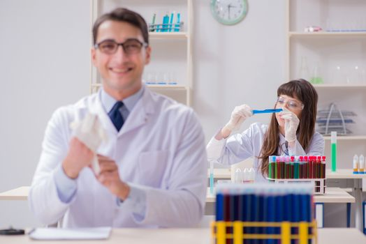 Two chemists working in lab experimenting