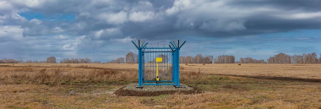Panoramic shot of a caged industrial gas station with barbwire on top of the fence. Yellow gas pipe in the middle of the cage, empty plate on the fence. Cloudy sky as a background. Siberia, Russia.