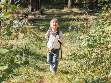 Curious boy is hiking in forest lit by sunlight. Outdoor leisure activity for kids. Child with binoculars and backpack. Summer journey fot little tourist. Adventure time.