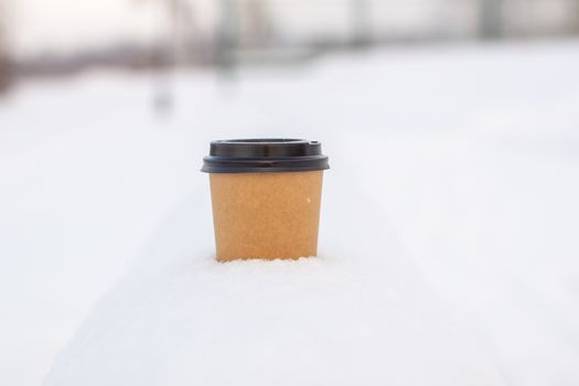 Cardboard coffee Cup in the snow in winter. Hot drink tea or coffee in a glass in winter outside.