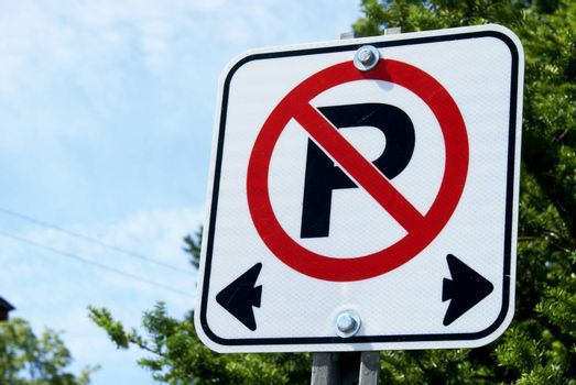 A horizontal closeup image focused on a no parking sign used in Canadian traffic laws.