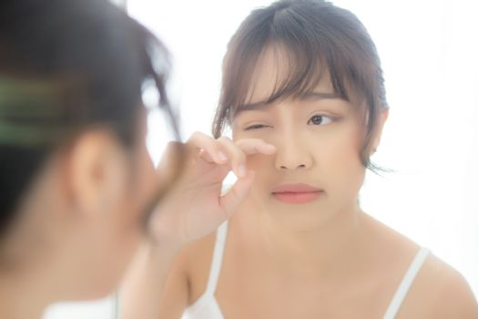 Beautiful and makeup young asian woman looking mirror aging on f