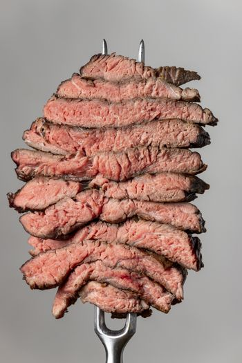 slices of a steak on grey background