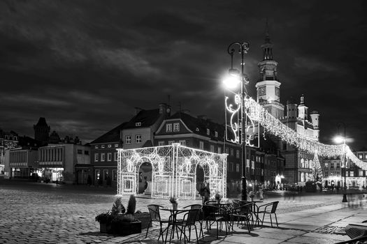 historic tenement houses and the renaissance town hall with Christmas decorations on the market square at night