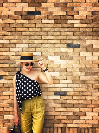 Portrait of young beautiful woman wearing a planter panama hat with brick wall background