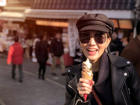 Young tourist woman eating ice cream cone covered with real gold leaf a famous street food in Japan