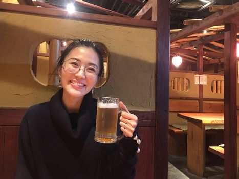 Happy smiling woman enjoy eating beer at classic restaurant in Japan