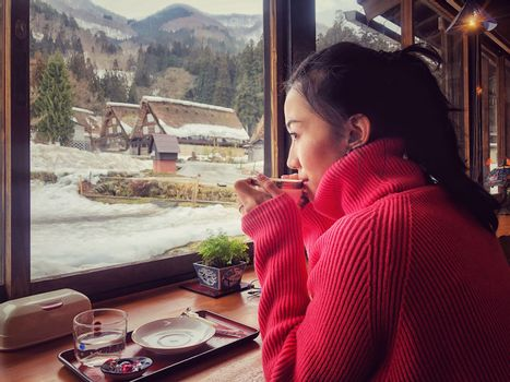 Woman tourist drinking coffee in the morning  and enjoying the winter snow view at Shirakawago village, Gifu, Japan.