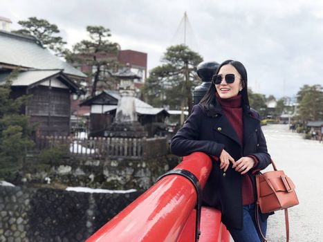 Happy woman tourist enjoy view in Red Nakabashi Bridge of Takayama, Japan