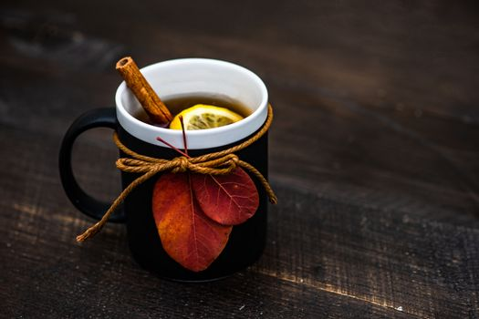 Cup of black tea and lemon on wooden background with copy space