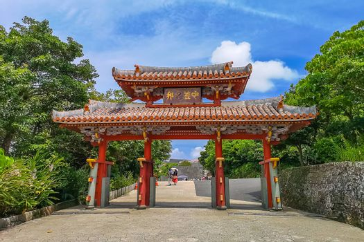 """Shureimon Gate in Shuri castle in Okinawa, Japan with blue sky. The wooden tablet that adorns the gate features Chinese characters that mean """"Land of Propriety"""""""