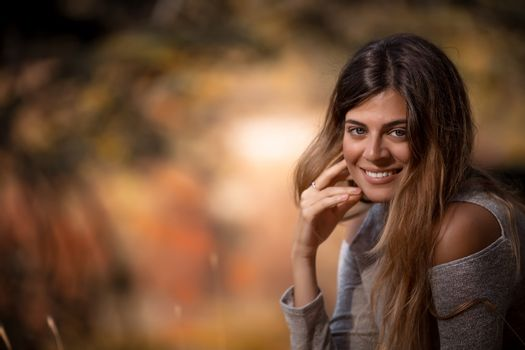 Portrait of a Beautiful Young Woman in Autumnal Park. Happy Smiling Girl Enjoying Warm Fall Nature. Female Outdoor Portrait